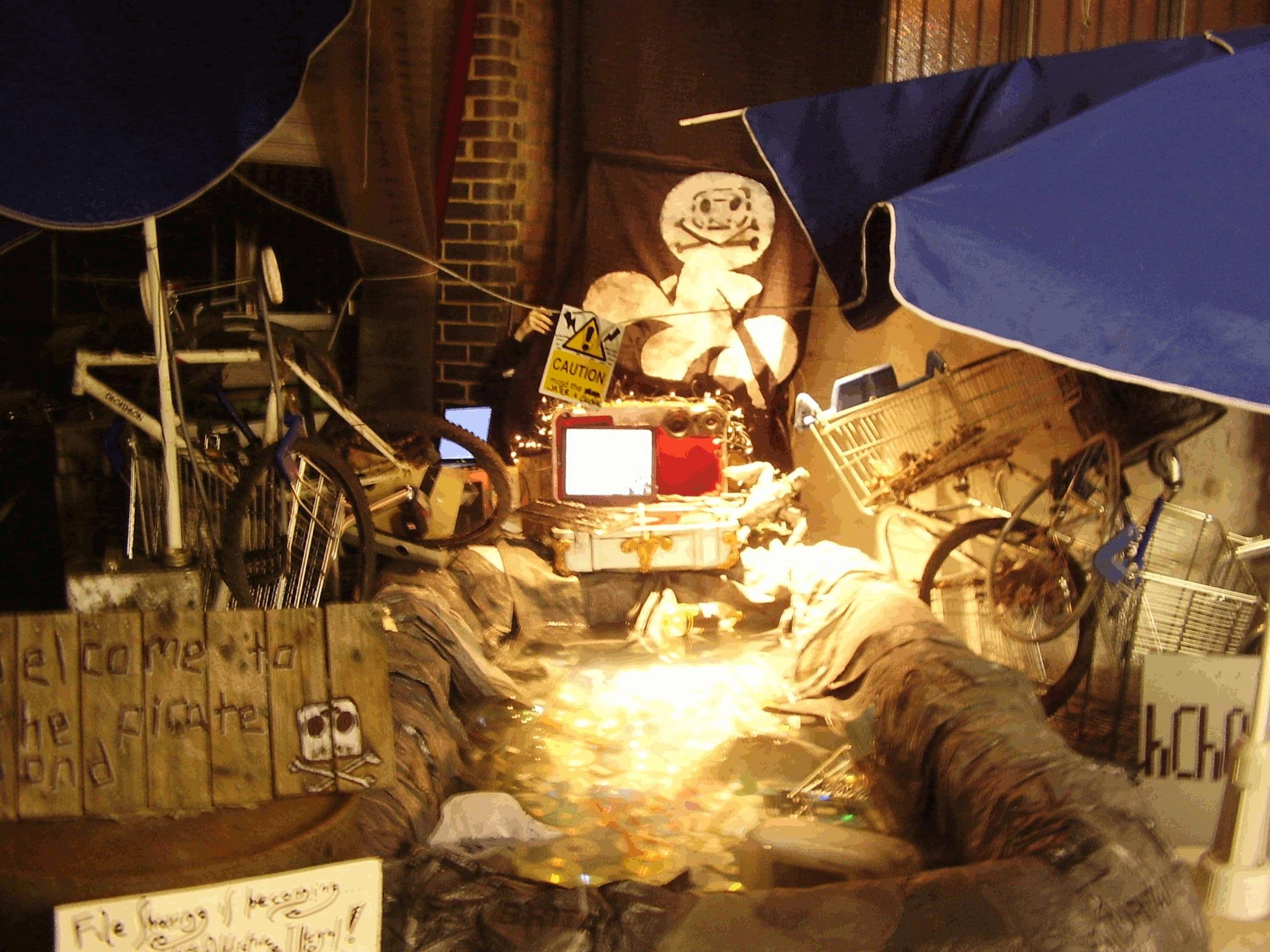 """Figura 5: Instalación """"Piratepond"""" del Hackney Crack House en la exhibición Temporary Autonomous Art en Londres, 2011, que incluye una Burnstation. La foto es de dominio público."""